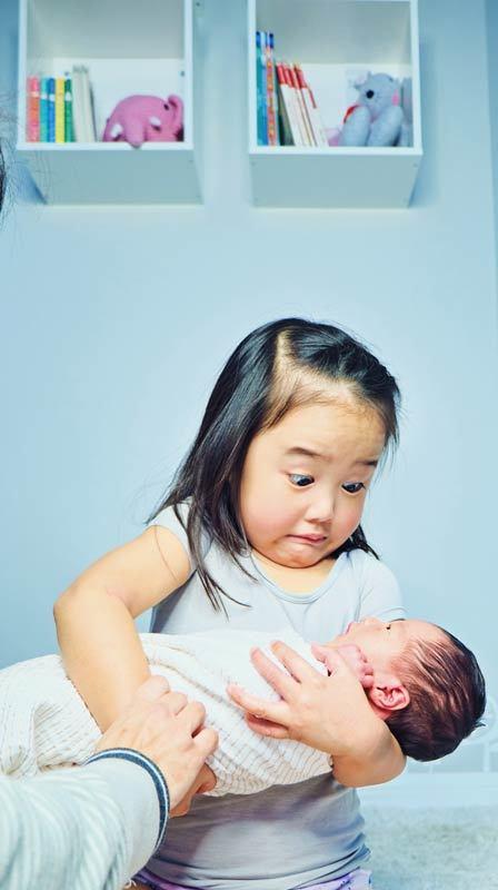 Реакция девочки, которой впервые дали подержать младшую сестру. Гораздо тяжелее тех кукол, на которых она тренировалась!