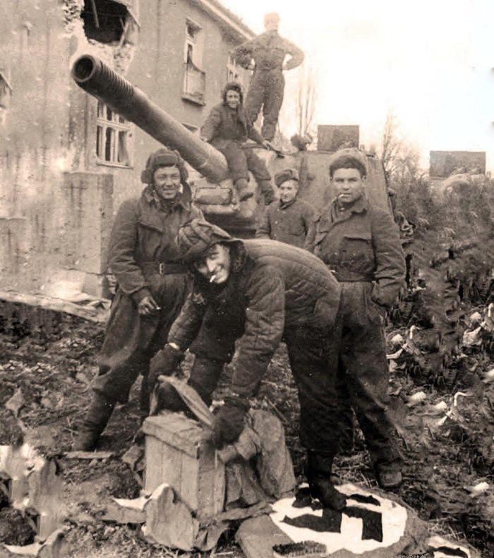 Красноармейцы чистят сапоги, стоя на нацистском флаге, 1945 год