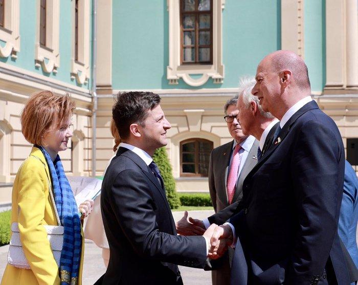 Член американской делегации поздравляет нового президента